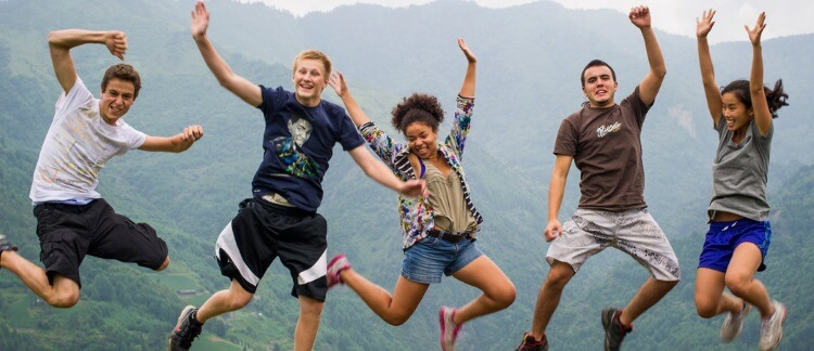 five excited students jumping of joy